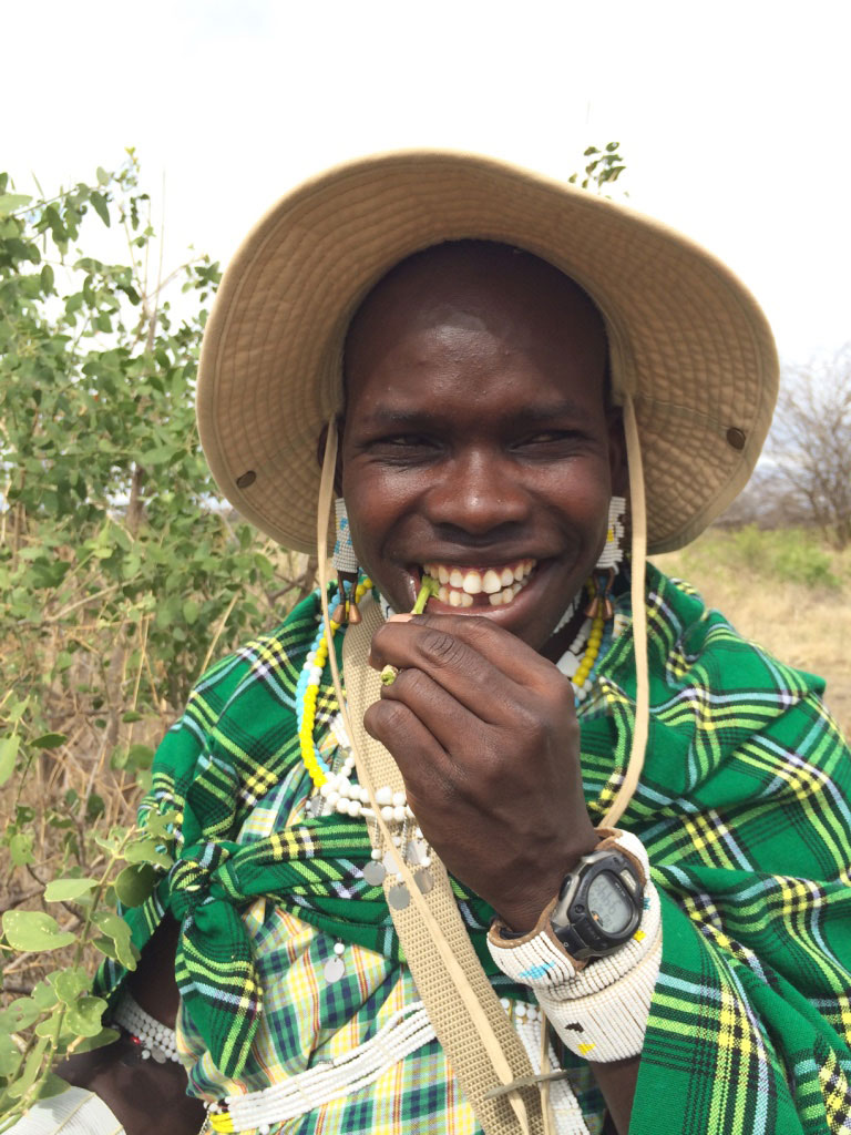 Maasai Seperti sharing a laugh while eating an herb out on Safari