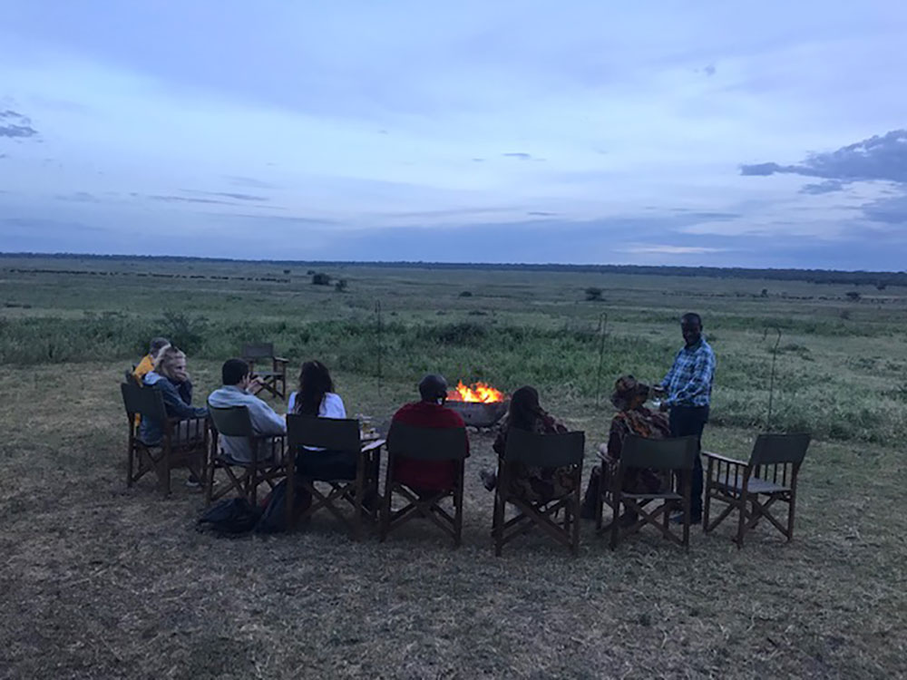 A gathering of safari travelers enjoying a sundowner by the fire in Tanzania
