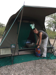 A Penwell traveler preparing to retire in her fly camping tent after a long day of safari