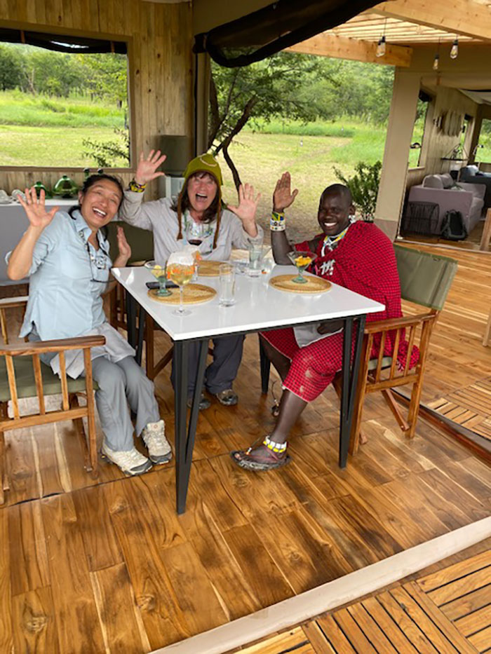 Enjoying a group safari sundowner in Tanzania with a tour guide at one of the camps