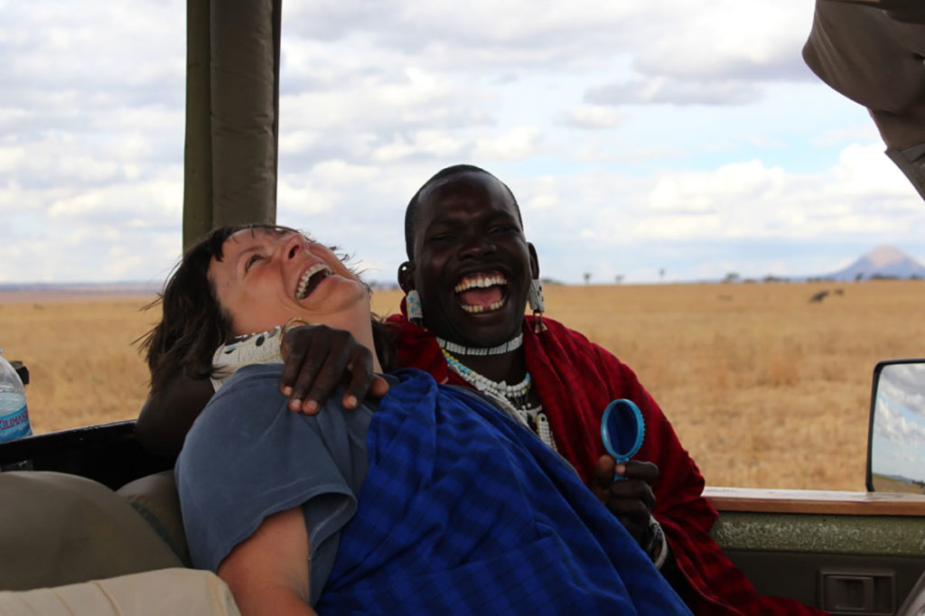 Kathy Harvey and safari Maasai tour guide Superti laughing on a game drive