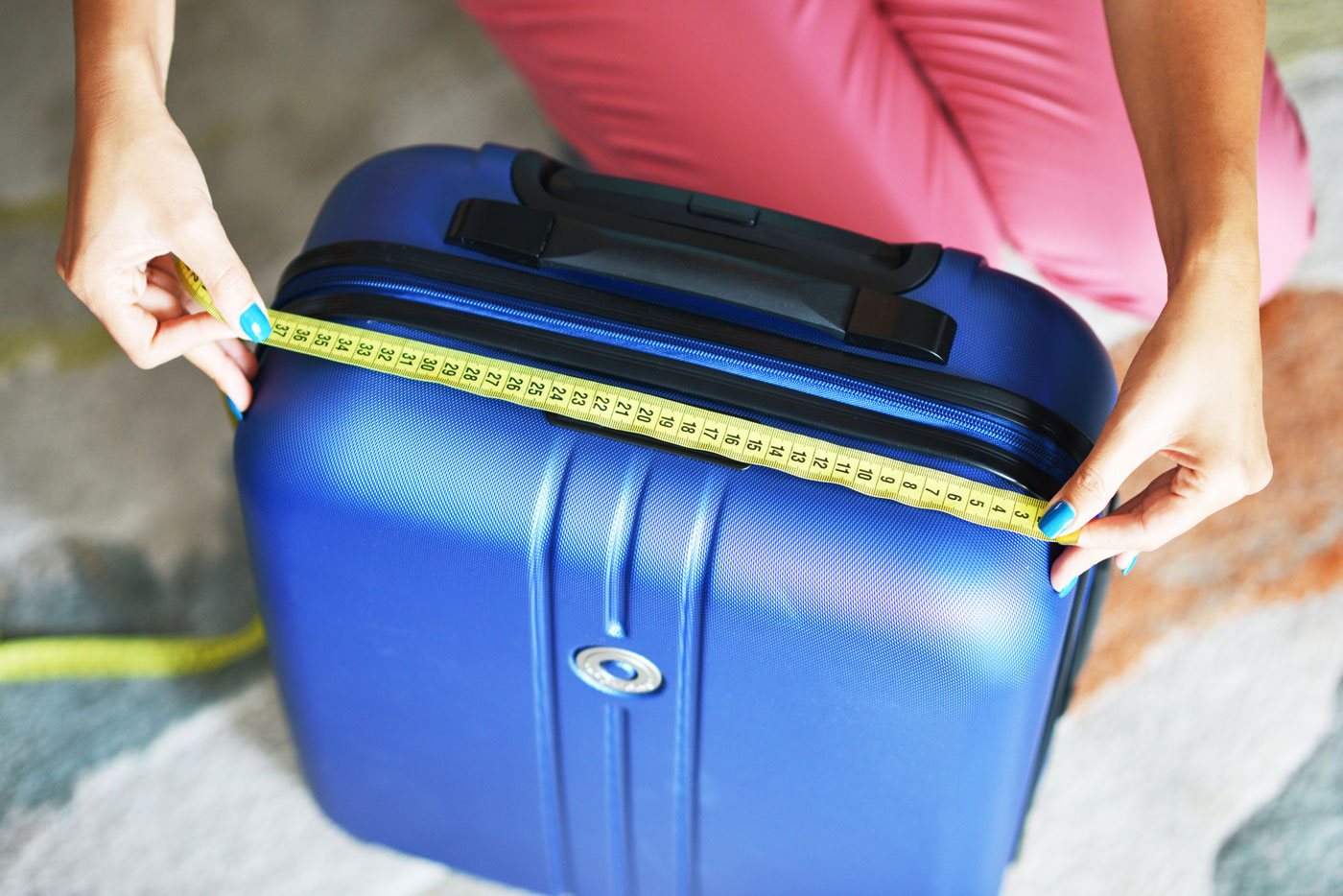 Traveler measuring their luggage before packing for vacation