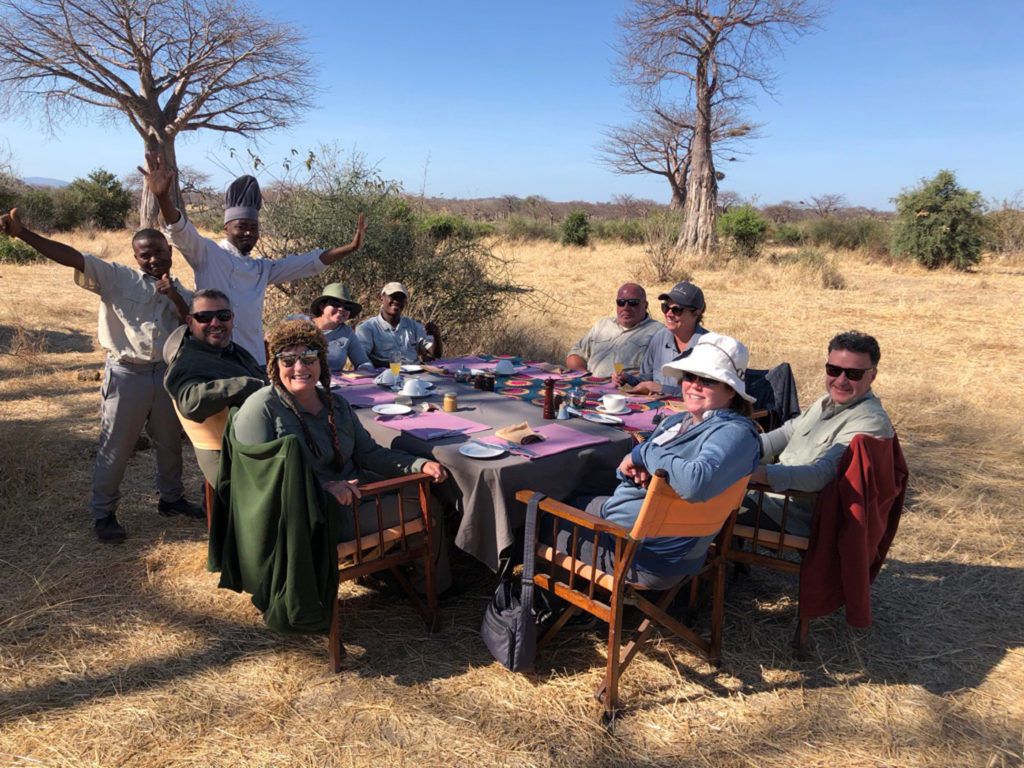 A happy group of safari-goers enjoying a breakfast with their chefs